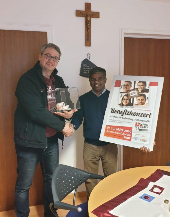 Stephan Otte überreicht Pater Thomas die Einnahmen aus dem Benefizkonzert als Spende